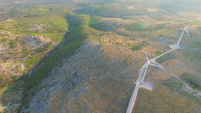 Flying above two elegant white wind turbines on green hills. Flying above two elegant ecological wind turbines on green sunlit hills stock video footage