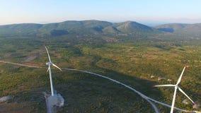 Flying above two elegant white wind turbines on green hills. Flying above two elegant ecological wind turbines on green sunlit hills stock video