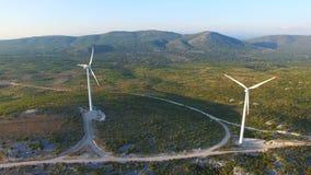 Flying above two elegant white wind turbines on green hills. Flying above two elegant ecological wind turbines on green sunlit hills stock footage