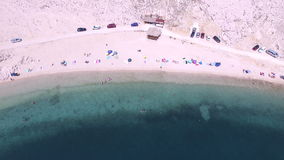 Flying above umbrellas and people on isolated beach of Pag island, Croatia stock video footage