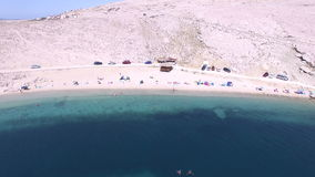 Flying above umbrellas and people on isolated beach of Pag island, Croatia stock video