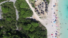 Flying above white sandy shore surrounded by trees stock video footage