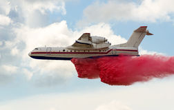 Flying aerial firefighting pour water Royalty Free Stock Photo