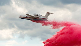 Flying aerial firefighting pour water Royalty Free Stock Image