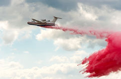 Flying aerial firefighting pour water Royalty Free Stock Images