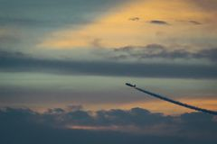 Flying Air Craft Under White Clouds at and Orange Sky at Sunset Stock Image