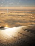 Flying on a Air Plane Wing Sunrise Golden Clouds Looking out a Window Stock Image