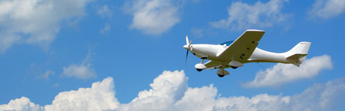 Flying aircraft banner. Small aircraft flying in the blue sky. Own custom production model Royalty Free Stock Images