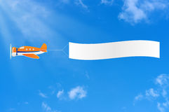 Flying aircraft carries banner. Stock Image