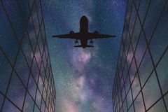 Flying aircraft between glass buildings at night Royalty Free Stock Images