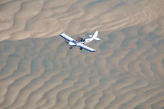 Flying aircraft over sand. Light sports aircraft, flying over the Great Sandy Strait in Australia Stock Image