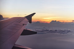 Flying aircraft wing on beautiful sunset Stock Images