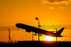 A flying airliner in the evening sky - a contour photography in the backlight stock image