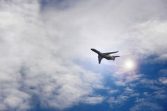 Flying airplane. Airplane flying in a cloudy sky with burst of sunlight Stock Photography