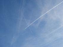 Flying airplane. Cross stich plane traces in the sky royalty free stock image