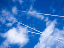 Flying airplane across the sky making air traces Royalty Free Stock Images
