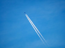 Flying airplane across the sky making air traces Stock Photography