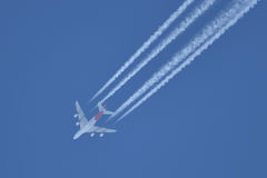 Flying airplane on the blue sky leaving white lines behind Stock Images