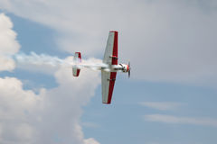 Flying airplane in the blue sky. Red - white plane jets of smoke in flight in a blue sky close-up stock photo