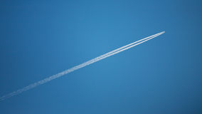 Flying airplane with contrails Stock Photos