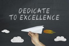 Flying airplane and Dedicated to Excellence written on chalkboard.  royalty free stock photography
