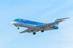 Flying Airplane KLM Cityhopper PH-KZI Fokker F70 is landing at Schiphol airport. Royalty Free Stock Image