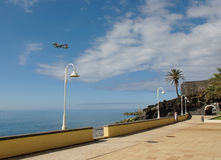 A flying airplane in the sky and beautiful seascape of Madeira royalty free stock photo