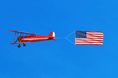 Flying airplane and USA flag American flag on blue sky. Royalty Free Stock Images