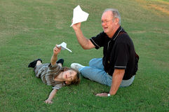 Flying airplanes with grandfather. A boy and his grandfather flying paper airplanes together in the grass Stock Photography