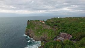 Flying along high cliffs of rocky ocean shore. Flight above high cliffs of the rocky shore of Indian Ocean with green vegetation on top. The coastline of Uluwatu stock video footage