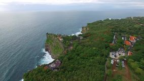Flying along high cliffs of rocky ocean shore. Flight above high cliffs of the rocky shore of Indian Ocean with green vegetation on top. The coastline of Uluwatu stock video