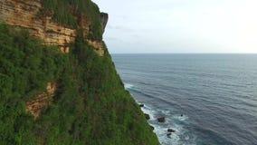 Flying along high cliffs of rocky ocean shore. Flight along the high cliffs of the rocky shore of the Indian Ocean. The frothy waves of the ocean break on sharp stock footage