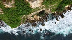 Flying along high cliffs of rocky ocean shore. Flight along high cliffs of rocky shore of Indian Ocean. Top down view of ocean frothy waves break on sharp rocks stock video