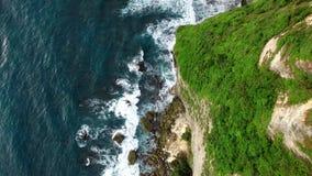 Flying along high cliffs of rocky ocean shore. Flight along high cliffs of rocky shore of Indian Ocean. Top down view of ocean frothy waves break on sharp rocks stock video footage