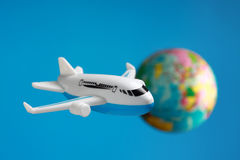 Flying around the world. Plastic toy plane flying on world globe in blue background Stock Photography
