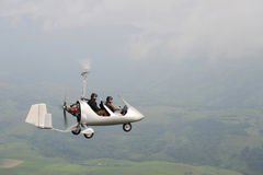 Flying autogyro. Autogyro flying over the tropical landscape Royalty Free Stock Images