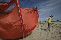 Flying away camp. Young man saving big orange camp on the beach Stock Image