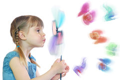 Flying away flowers. Little girl blowing at a flower and some flowers lying away from it Stock Photo