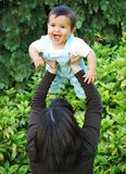 The Joy's of Motherhood!. Multiracial baby with big brown eyes being held high above mothers head laughing joyfully learning to trust the motion of up and Stock Photo