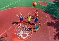 Flying ball to basket top view during basketball. Flying ball to the basket top view during basketball game with kids standing on the ground down stock photos