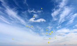 Flying balloon. Yellow flying balloon in the cloudy sky royalty free stock photo