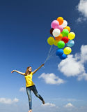 Flying with balloons. Happy young woman holding colorful balloons and flying over a green meadow royalty free stock images