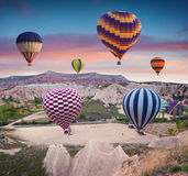 Flying on the balloons early morning in Cappadocia. Colorful sunrise in Red Rose valley, Goreme village location, Turkey, Asia. Artistic style post processed Stock Photos