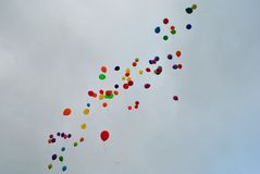Flying balloons in the sky. Flying colorful balloons in the grey sky Stock Image