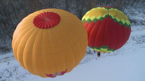 Flying balloons in winter. Two bright flying balloons over land stock video footage