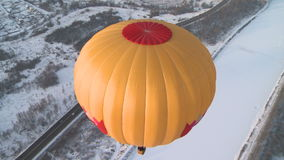 Flying balloons in winter. Two bright flying balloons over land stock footage