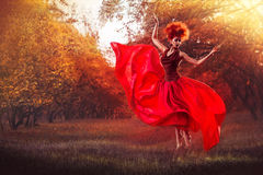 Flying Beautiful girl on a background of falling leaves. Royalty Free Stock Photography
