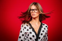 Flying beautiful hair. Attractive young woman in spectacles with beautiful long flying hair over red background. Studio shot. Beauty, fashion concept. Optics stock photography