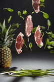Flying beef steaks and basil leaves, a pineapple and spring onions. A brilliant photo of flying beef steaks and basil leaves, a pineapple and spring onions in stock image