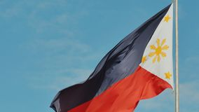 Flying bicolor flag of the Philippines with central golden sun representing the provinces and stars the islands. Flying bicolor flag of the Philippines with stock video footage